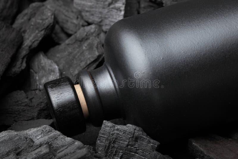 Αρχικό μαύρο μπουκάλι μεταλλινών της βότκας ή του tequila ή άλλου ηδύποτου Στο υπόβαθρο ξυλάνθρακα Μαύρη έκδοση δημιουργικός Πιεί στοκ εικόνες