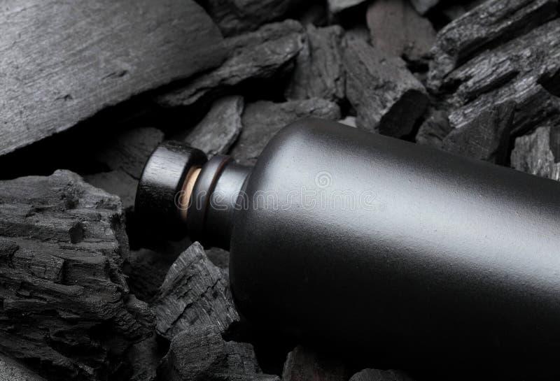 Αρχικό μαύρο μπουκάλι μεταλλινών της βότκας ή του tequila ή άλλου ηδύποτου Στο υπόβαθρο ξυλάνθρακα Μαύρη έκδοση δημιουργικός Πιεί στοκ φωτογραφία