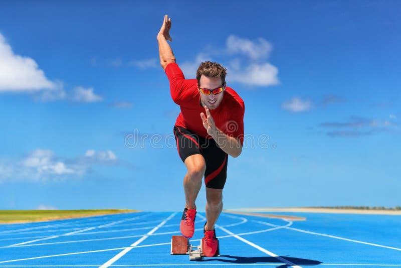 Αρχικό τρέξιμο αθλητών δρομέων στην έναρξη της διαδρομής τρεξίματος στις μπλε τρέχοντας διαδρομές στο υπαίθριο στάδιο αθλητισμού  στοκ φωτογραφία με δικαίωμα ελεύθερης χρήσης