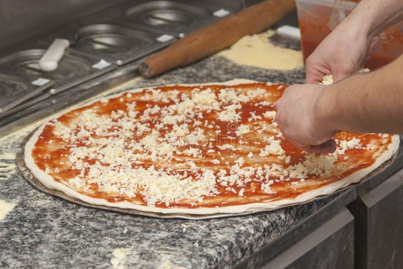 Αρχιμάγειρας ατόμων με την ακατέργαστη πίτσα στοκ εικόνα με δικαίωμα ελεύθερης χρήσης