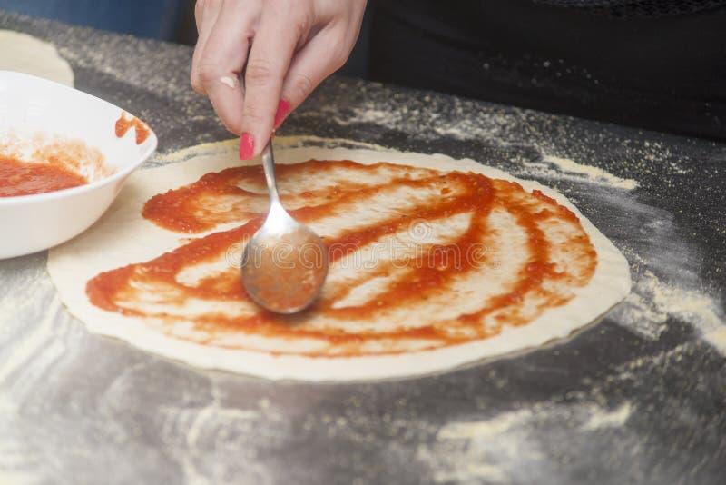Αρχιμάγειρας γυναικών με την ακατέργαστη ζύμη στοκ φωτογραφία