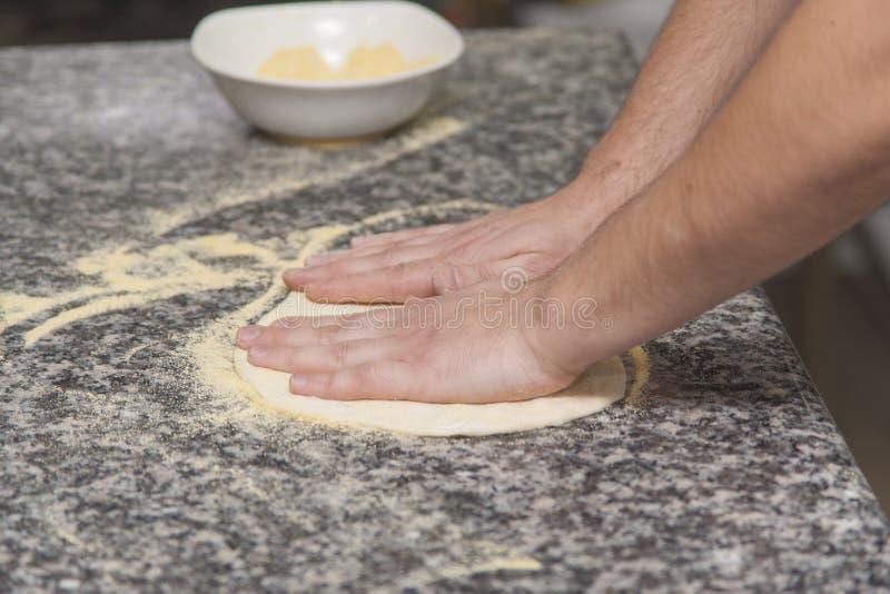 Αρχιμάγειρας γυναικών με την ακατέργαστη ζύμη στοκ εικόνα