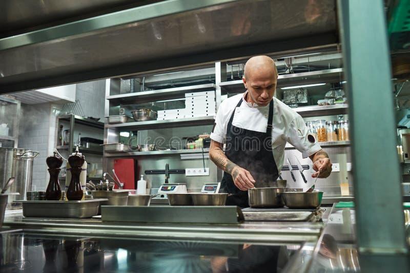 Αρχιμάγειρας εστιατορίων Ο συγκεντρωμένος νέος αρχιμάγειρας στη μαύρη ποδιά μαγειρεύει στη σύγχρονη κουζίνα εστιατορίων του στοκ φωτογραφία