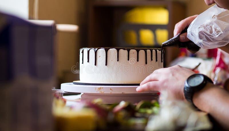 Αρχιμάγειρας ζύμης στην κουζίνα που διακοσμεί ένα κέικ της σοκολάτας, φρούτα, στοκ φωτογραφίες