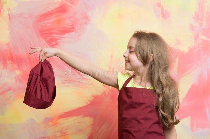 Αρχιμάγειρας κοριτσιών ή ευτυχές καπέλο μαγείρων λαβής μωρών, μαγειρεύοντας ποδιά στοκ φωτογραφίες