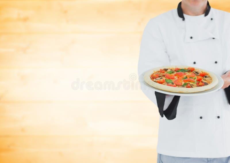 Αρχιμάγειρας με την πίτσα ενάντια στη μουτζουρωμένη κίτρινη ξύλινη επιτροπή στοκ εικόνες με δικαίωμα ελεύθερης χρήσης