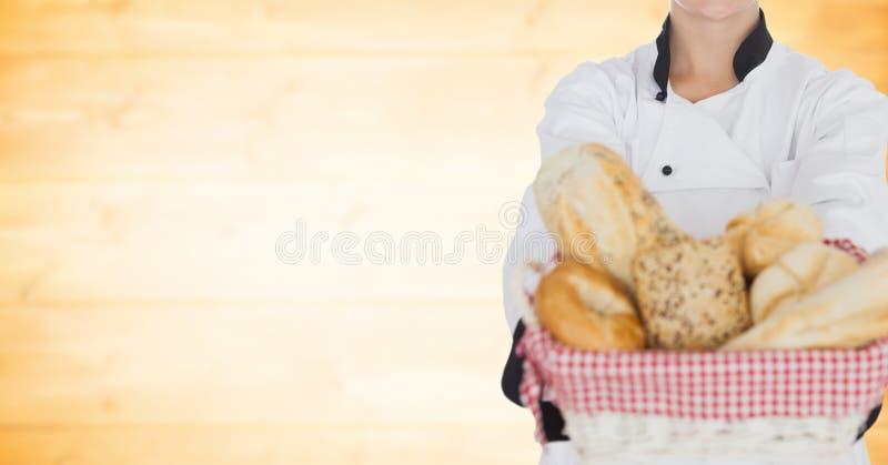 Αρχιμάγειρας με το ψωμί ενάντια στη μουτζουρωμένη κίτρινη ξύλινη επιτροπή στοκ φωτογραφία με δικαίωμα ελεύθερης χρήσης