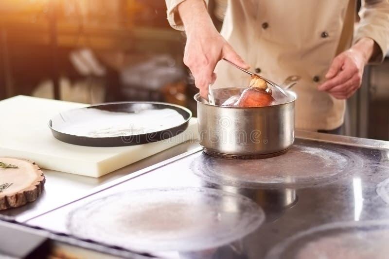 Αρχιμάγειρας που βάζει έξω την κνήμη αρνιών από την κατσαρόλλα στοκ εικόνες με δικαίωμα ελεύθερης χρήσης