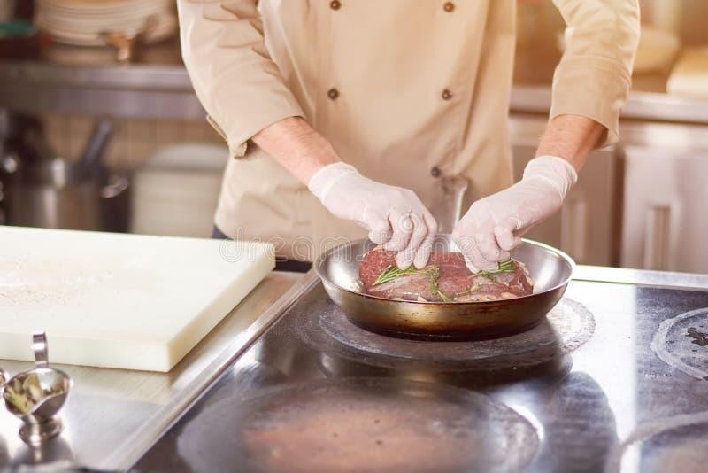 Αρχιμάγειρας που βάζει στο κρέας στο τηγάνισμα του τηγανιού στοκ φωτογραφίες