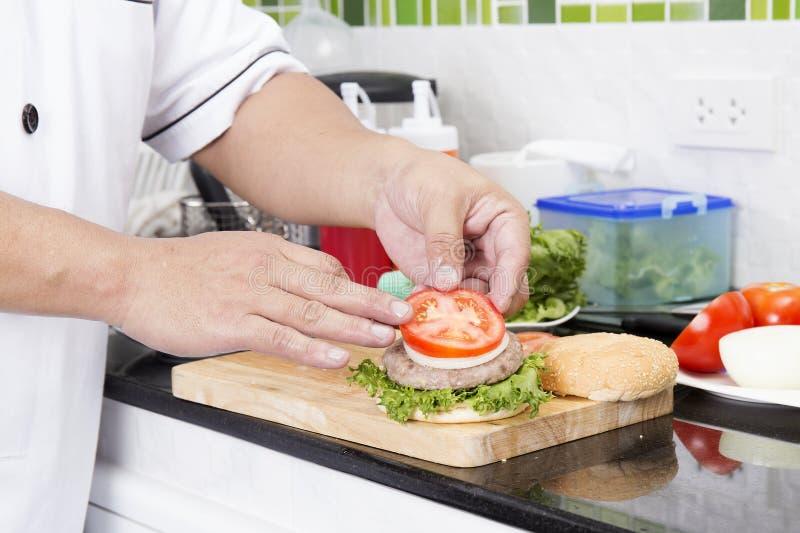 Αρχιμάγειρας που βάζει τη φέτα της ντομάτας στο κουλούρι χάμπουργκερ στοκ εικόνα