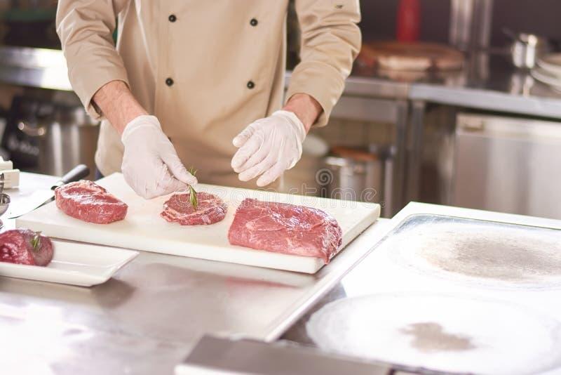 Αρχιμάγειρας που βάζει το δεντρολίβανο στην μπριζόλα στοκ εικόνες με δικαίωμα ελεύθερης χρήσης