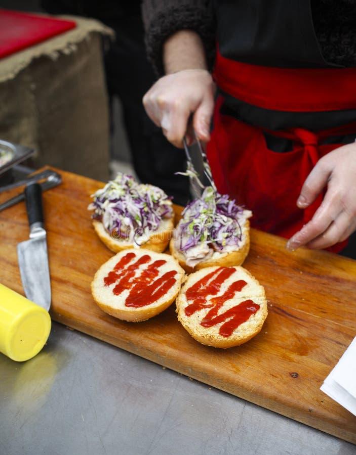 Αρχιμάγειρας που καθιστά τα burgers βόειου κρέατος υπαίθρια στην ανοικτή κουζίνα στοκ φωτογραφία