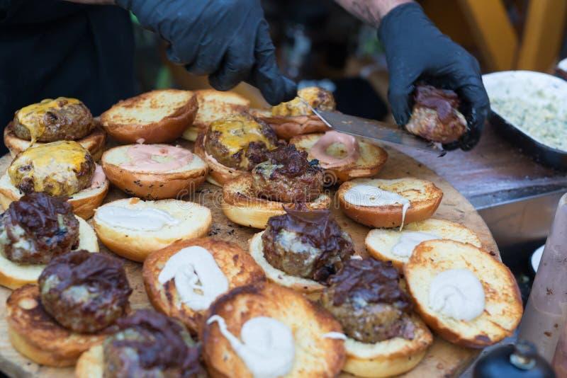 Αρχιμάγειρας που καθιστά τα burgers βόειου κρέατος υπαίθρια στο ανοικτό γεγονός φεστιβάλ τροφίμων κουζινών διεθνές στοκ εικόνες