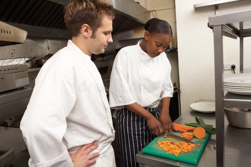 Αρχιμάγειρας που καθοδηγεί τον εκπαιδευόμενο στοκ εικόνες