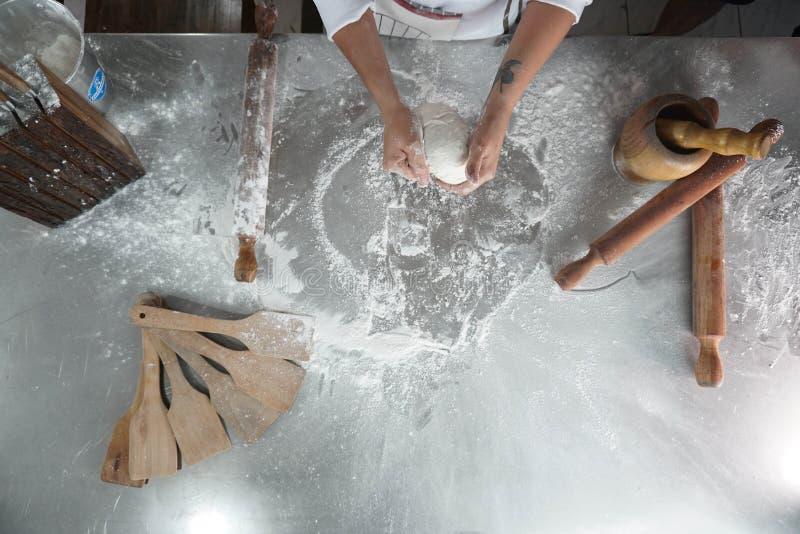 Αρχιμάγειρας που κατασκευάζει τη ζύμη πιτσών στοκ εικόνες