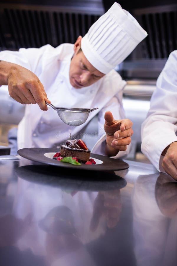 Αρχιμάγειρας που κοσκινίζει τη ζάχαρη τήξης πέρα από ένα επιδόρπιο στοκ φωτογραφίες με δικαίωμα ελεύθερης χρήσης