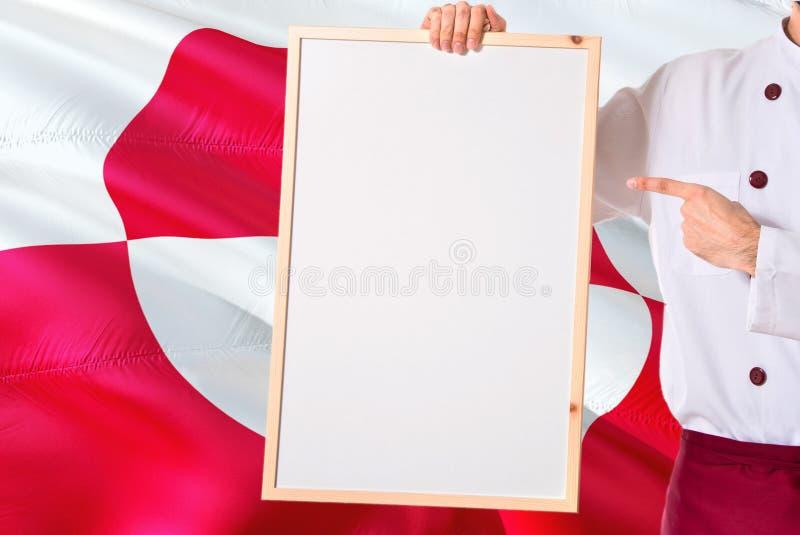 Αρχιμάγειρας που κρατά τις κενές επιλογές whiteboard στο υπόβαθρο σημαιών της Γροιλανδίας Μάγειρας που φορά το ομοιόμορφο δείχνον στοκ εικόνες