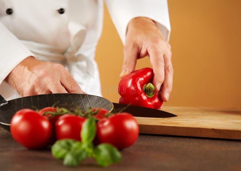Αρχιμάγειρας που κόβει ένα φρέσκο κόκκινο γλυκό πιπέρι στοκ φωτογραφία με δικαίωμα ελεύθερης χρήσης