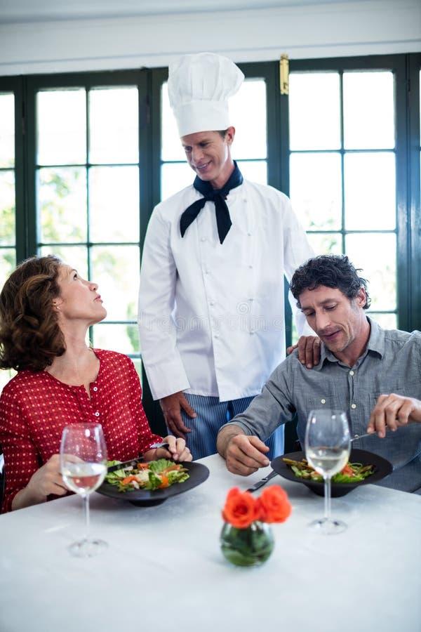 Αρχιμάγειρας που μιλά στο ζεύγος στοκ εικόνα