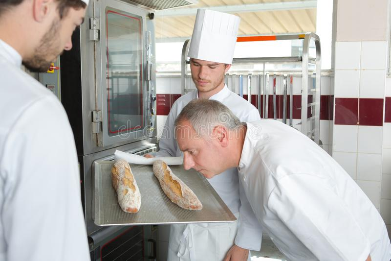 Αρχιμάγειρας που μυρίζει το πρόσφατα ψημένο baguette στοκ φωτογραφίες με δικαίωμα ελεύθερης χρήσης