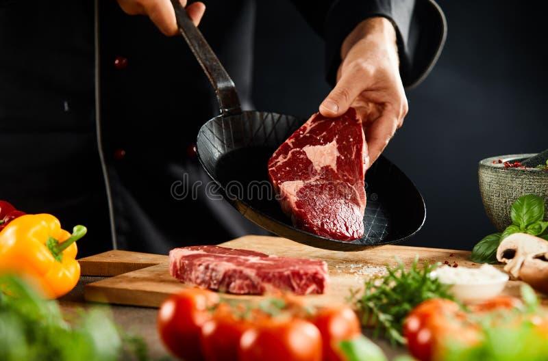 Αρχιμάγειρας που προετοιμάζει μια τρυφερή ακατέργαστη μπριζόλα βόειου κρέατος για το μαγείρεμα στοκ φωτογραφία