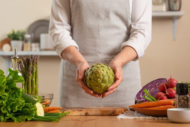 Αρχιμάγειρας που προετοιμάζει την αγκινάρα Η έννοια της απώλειας των υγιών και θρεπτικών τροφίμων, detox, vegan κατανάλωση, διατρ στοκ εικόνες