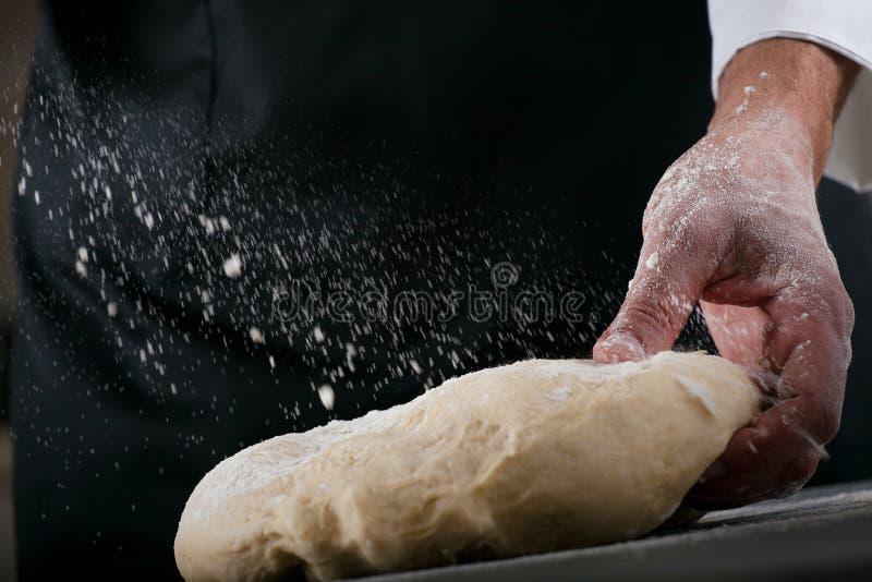 Αρχιμάγειρας που προετοιμάζει τη ζύμη, που κατασκευάζει τη ζύμη από τα αρσενικά χέρια στο αρτοποιείο στοκ φωτογραφία με δικαίωμα ελεύθερης χρήσης