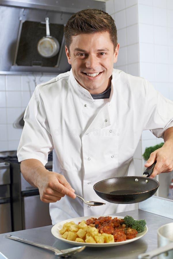 Αρχιμάγειρας που προσθέτει τη σάλτσα στο πιάτο στην κουζίνα εστιατορίων στοκ φωτογραφία