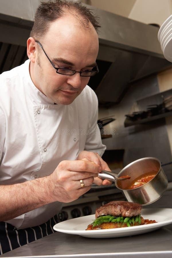 Αρχιμάγειρας που προσθέτει τη σάλτσα στο πιάτο στο εστιατόριο στοκ εικόνες