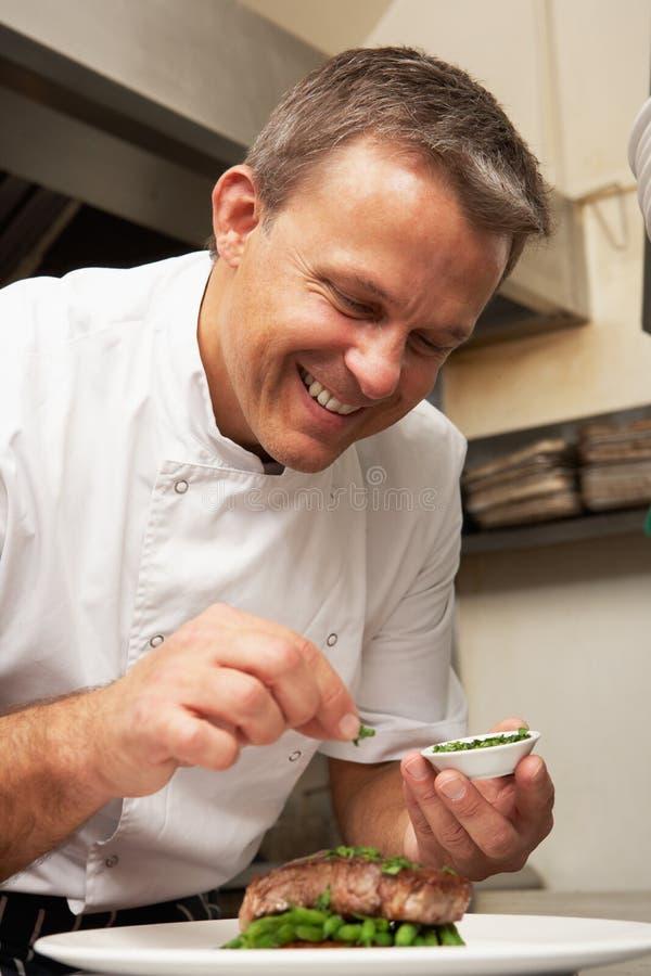 Αρχιμάγειρας που προσθέτει το καρύκευμα στο πιάτο στην κουζίνα στοκ φωτογραφία με δικαίωμα ελεύθερης χρήσης