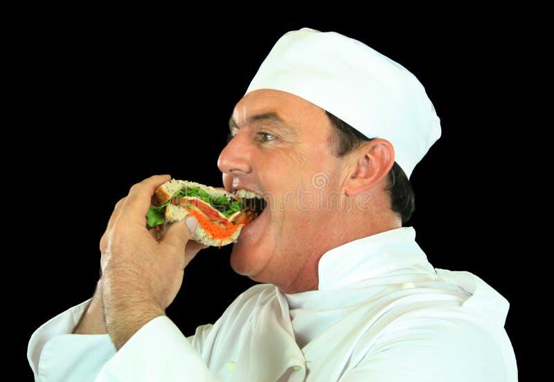 αρχιμάγειρας που τρώει το σάντουιτς στοκ εικόνα