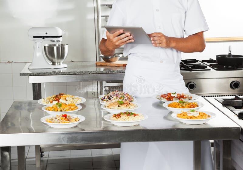 Αρχιμάγειρας που χρησιμοποιεί τον ψηφιακό υπολογιστή στην κουζίνα στοκ φωτογραφία με δικαίωμα ελεύθερης χρήσης