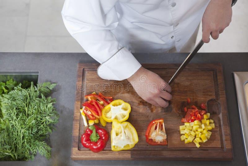 Αρχιμάγειρας που χωρίζει σε τετράγωνα τα κόκκινα και κίτρινα πιπέρια κουδουνιών στοκ φωτογραφίες