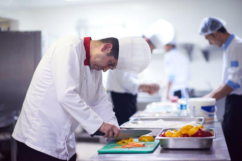 Αρχιμάγειρας στα λαχανικά φετών κουζινών ξενοδοχείων με το μαχαίρι στοκ εικόνα