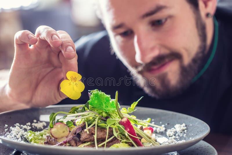 Αρχιμάγειρας στο ξενοδοχείο ή εστιατόριο που προετοιμάζει τη σαλάτα με τα κομμάτια του βόειου κρέατος στοκ φωτογραφία με δικαίωμα ελεύθερης χρήσης