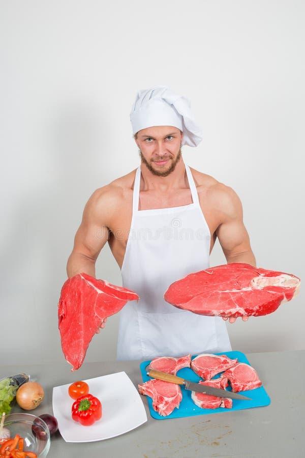 Αρχιμάγειρας bodybuilder που προετοιμάζει τα μεγάλα χοντρά κομμάτια ακατέργαστου στοκ φωτογραφία με δικαίωμα ελεύθερης χρήσης