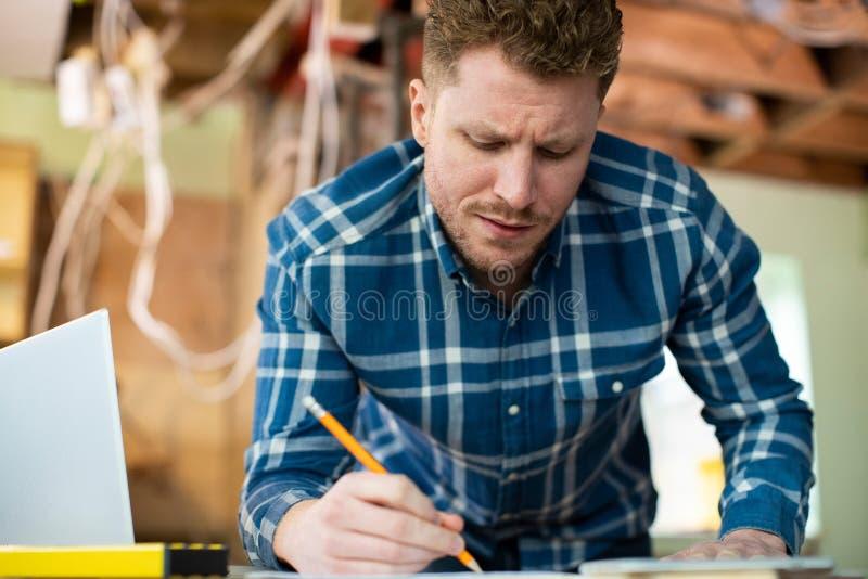 Αρχιτέκτονας μέσα στο σπίτι που ανακαινίζεται εργαζόμενος στα σχέδια που χρησιμοποιούν το lap-top στοκ εικόνες