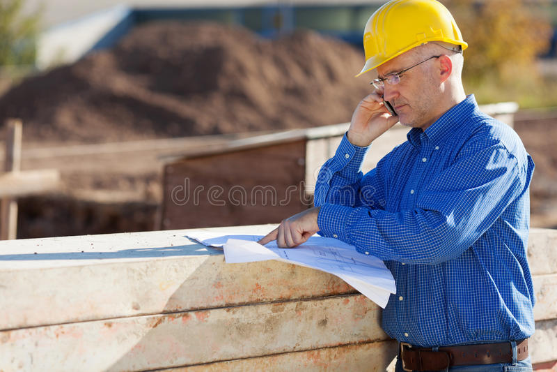 Αρχιτέκτονας που δείχνει στο σχεδιάγραμμα χρησιμοποιώντας το κινητό τηλέφωνο στοκ εικόνα