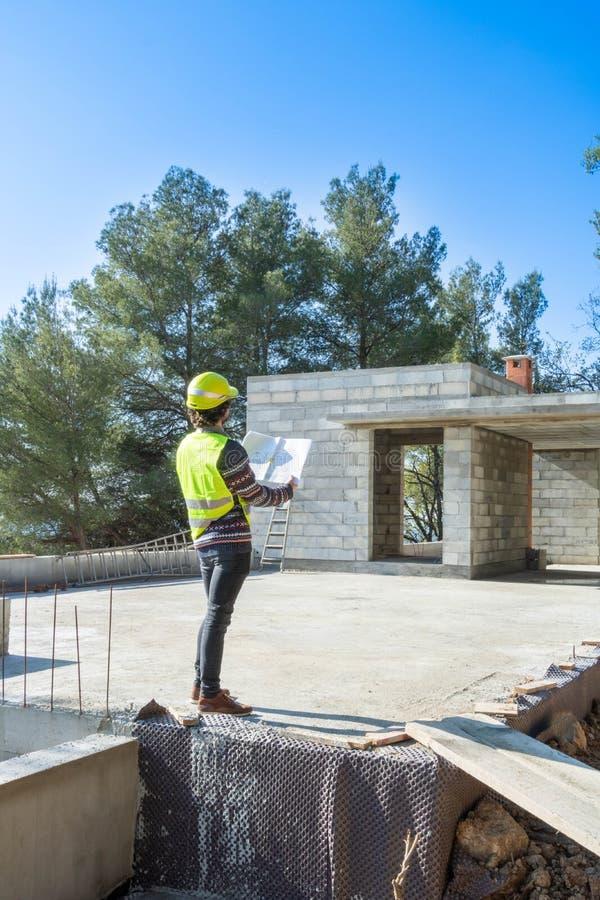 Αρχιτέκτονας που ελέγχει τα σχέδια ενός σπιτιού κάτω από την κατασκευή στοκ φωτογραφία με δικαίωμα ελεύθερης χρήσης
