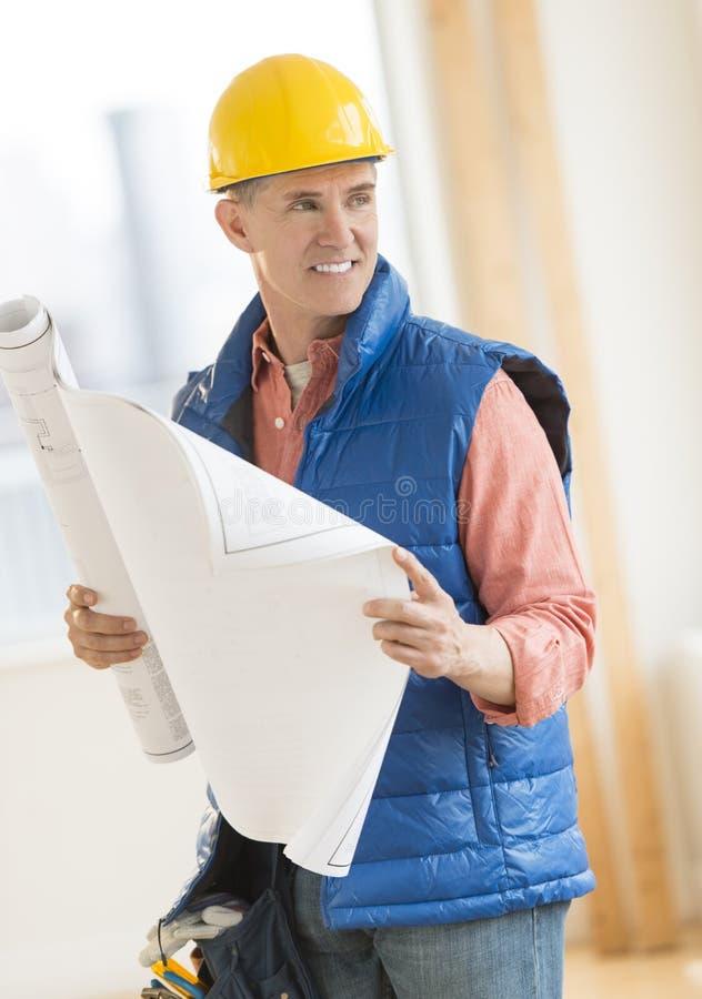 Αρχιτέκτονας που εξετάζει μακριά ενώ σχεδιάγραμμα εκμετάλλευσης την κατασκευή S στοκ φωτογραφία με δικαίωμα ελεύθερης χρήσης