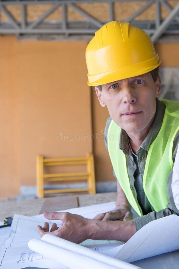 Αρχιτέκτονας που εξετάζει τη κάμερα εργαζόμενος με τα σχεδιαγράμματα στο εργοτάξιο οικοδομής στοκ εικόνα με δικαίωμα ελεύθερης χρήσης