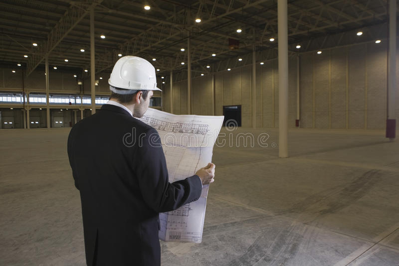 Αρχιτέκτονας που εξετάζει το σχεδιάγραμμα στην αποθήκη εμπορευμάτων στοκ φωτογραφία