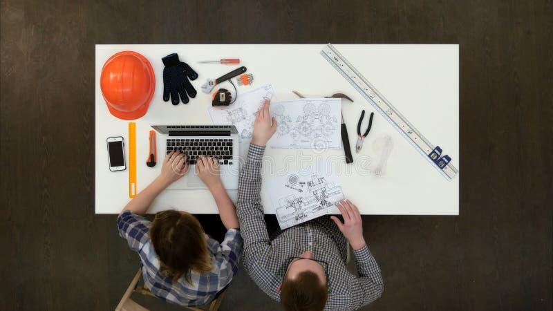 Αρχιτέκτονας που εργάζεται στα σχεδιαγράμματα η θηλυκή δακτυλογράφηση συναδέλφων στο lap-top στοκ εικόνες