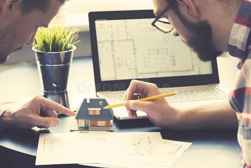 Αρχιτέκτονας που παρουσιάζει πρότυπο καινούργιων σπιτιών στον πελάτη στο γραφείο στοκ εικόνα με δικαίωμα ελεύθερης χρήσης