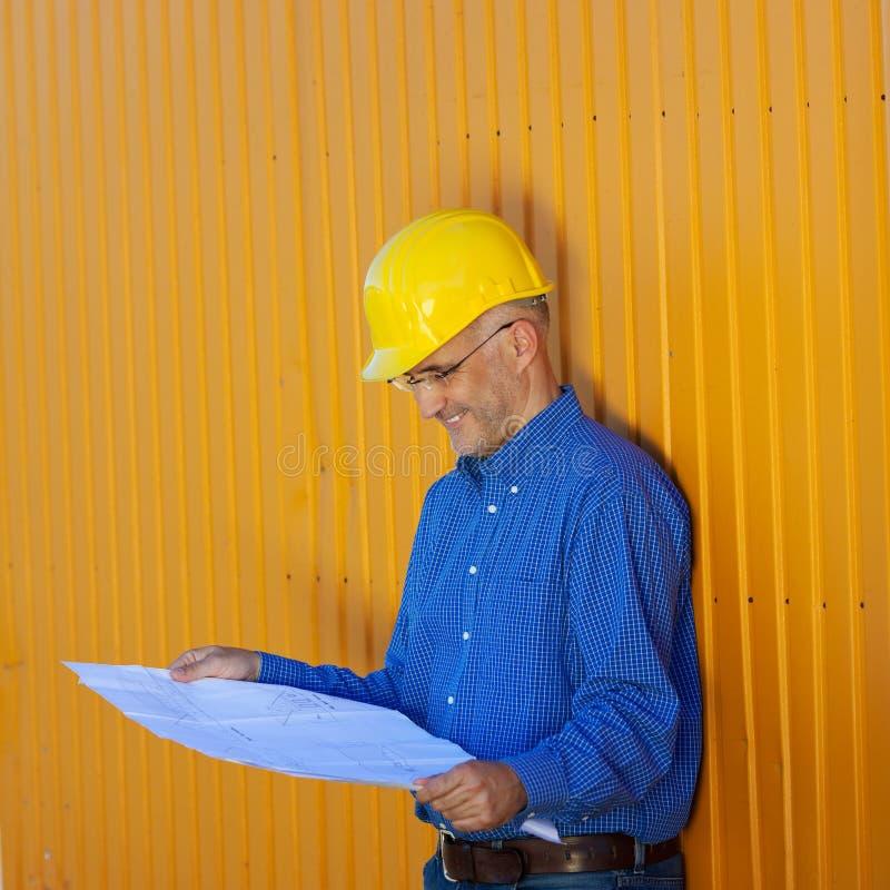 Αρχιτέκτονας που φορά Hardhat αναλύοντας την μπλε τυπωμένη ύλη στοκ φωτογραφίες