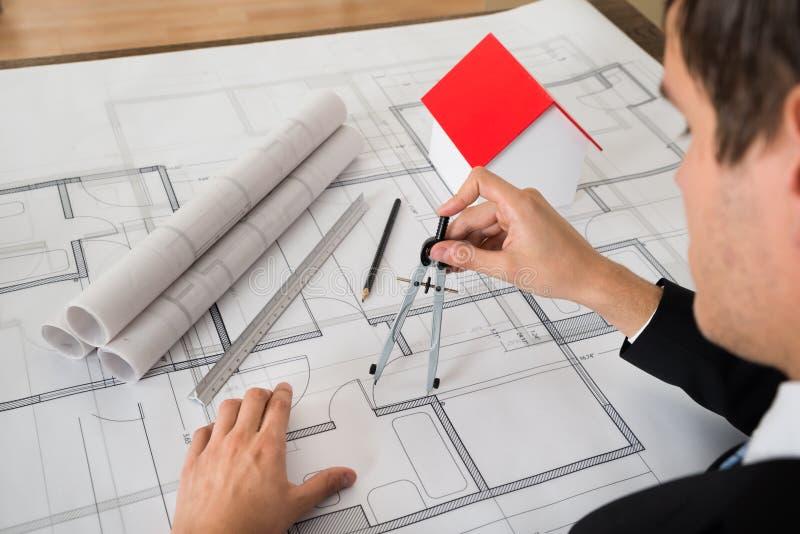 Αρχιτέκτονας που χρησιμοποιεί την πυξίδα στο σχεδιάγραμμα στοκ φωτογραφία με δικαίωμα ελεύθερης χρήσης