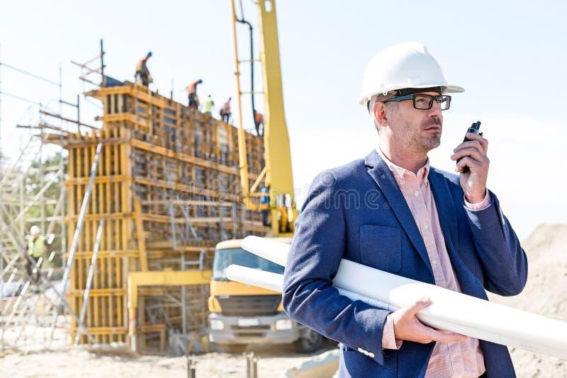 Αρχιτέκτονας που χρησιμοποιεί walkie-talkie κρατώντας τα σχεδιαγράμματα στο εργοτάξιο οικοδομής στοκ εικόνα