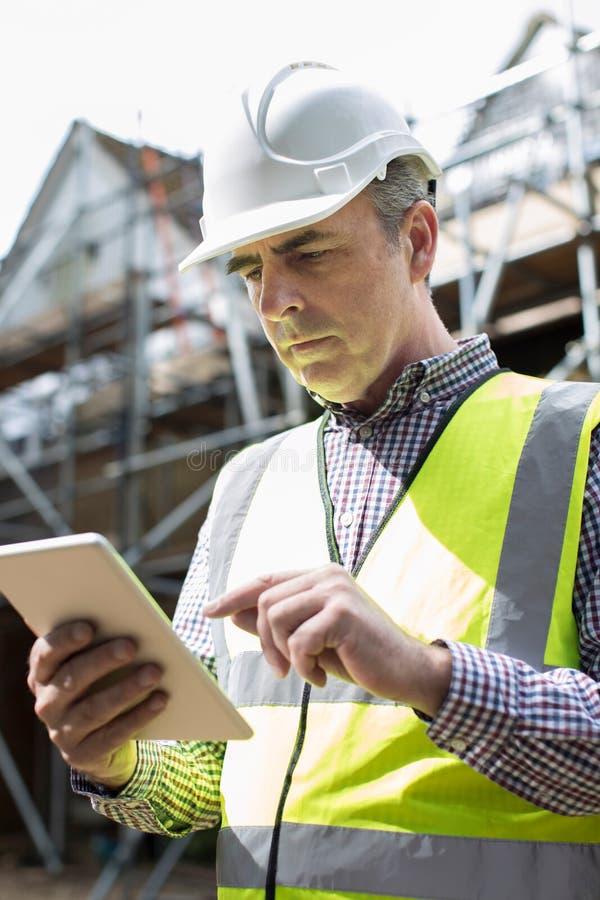 Αρχιτέκτονας στο εργοτάξιο που χρησιμοποιεί την ψηφιακή ταμπλέτα στοκ φωτογραφίες