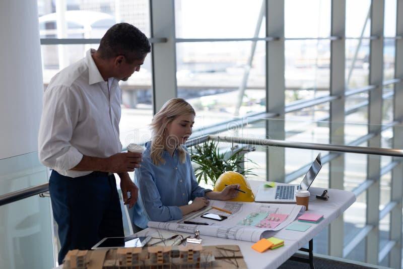 Αρχιτέκτονες Καυκασίων που αλληλεπιδρούν ο ένας με τον άλλον στο γραφείο στην αρχή στοκ εικόνες