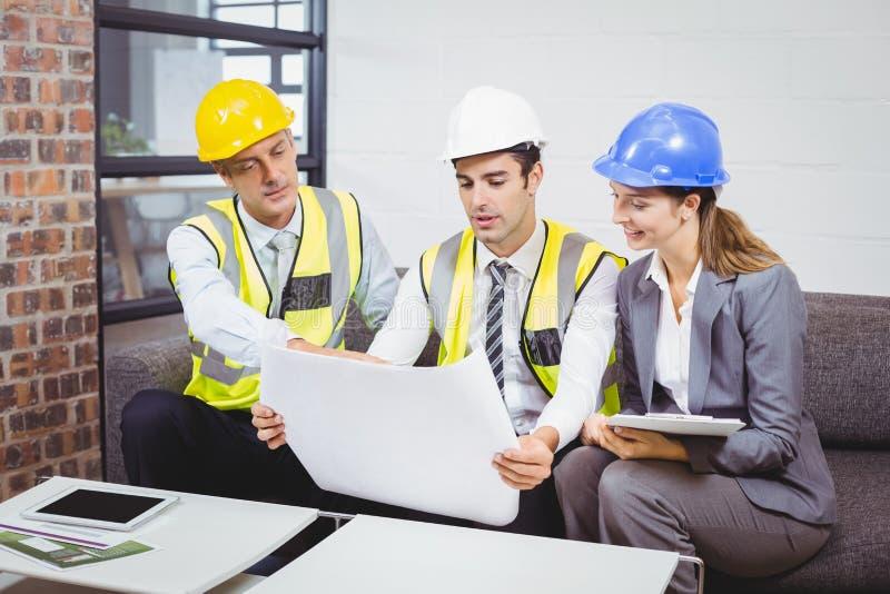 Αρχιτέκτονες που συζητούν με το σχεδιάγραμμα στοκ φωτογραφία